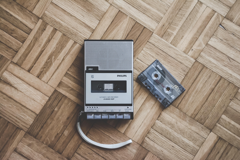 Tape recorder and cassette tape on wood floor. Photo by Simone Acquaroli on Unsplash.